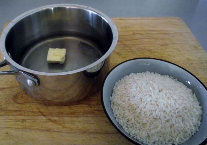 Ingredients for white rice: water, butter, and salt in a sauce-pan and white rice in a bowl.