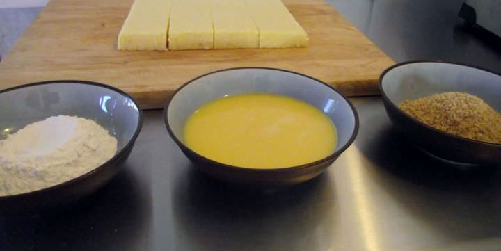 Preparing to bread polenta squares, with flour, egg, and breadcrumbs.