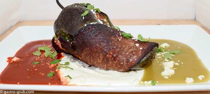 Chile relleno wrapped with flank steak and served with chili sauce, crema, and tomatillo sauce.