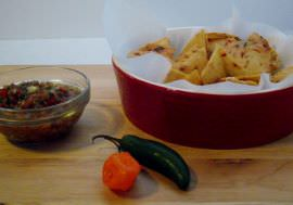 Tortilla chips, salsa, and chili peppers.