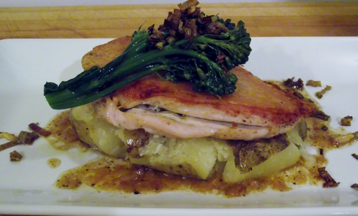 Chicken under a brick, smashed potato, and broccoli rabe on a plate.