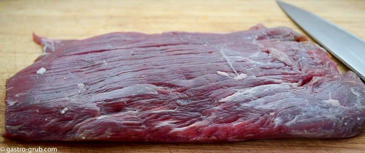 Flank steak on a cutting board.