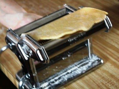 Rolling pasta dough through a pasta machine.