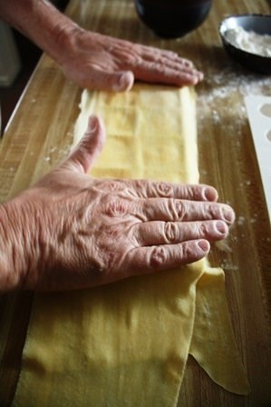 Covering raviolis with second pasta sheet.