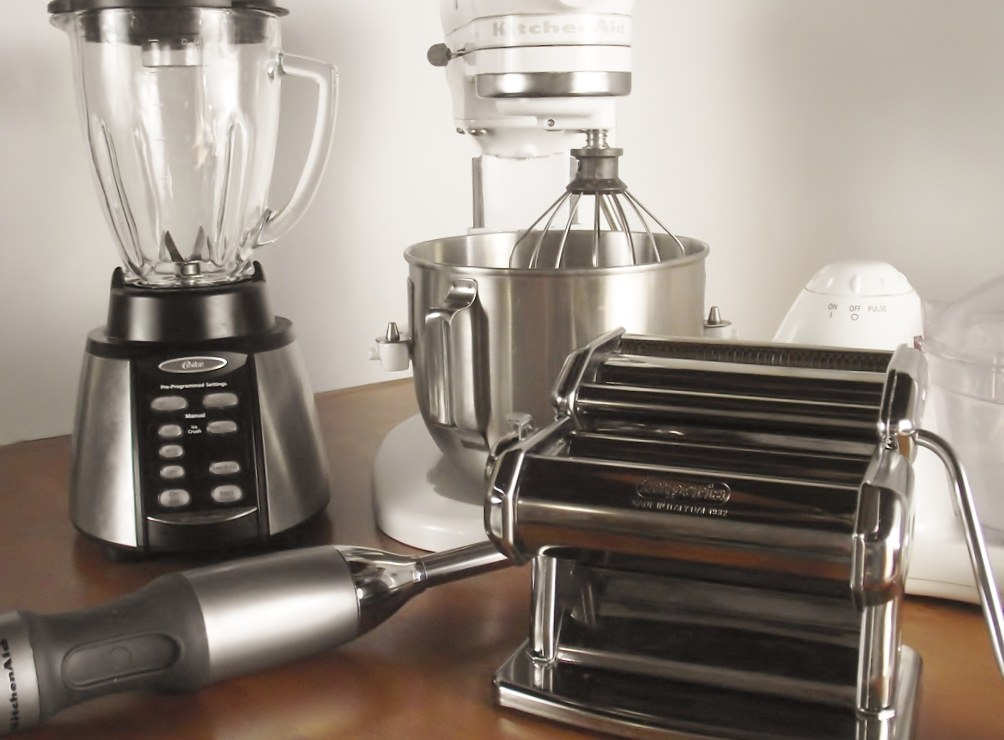Kitchen appliances: blender, stand mixer, pasta machine, food processor, and a stick blender.
