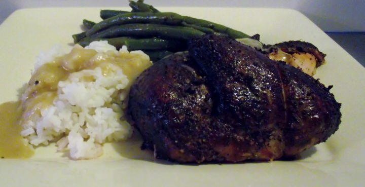 Smoked chicken, rice with smoked chicken gravy, and green beans on a plate.